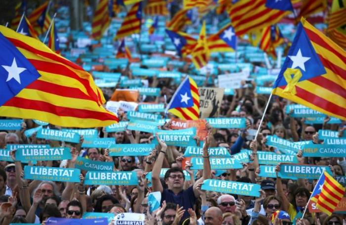 People wave separatisy Catalan flags and placards during a demonstration organised by Catalan pro-independence movements ANC (Catalan National Assembly) and Omnium Cutural, following the imprisonment of their two leaders in Barcelona